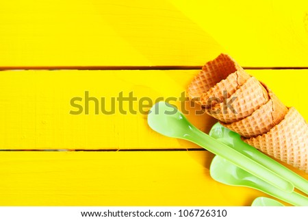 Ice cream cones and green plastic spoons on yellow table with copy space - stock photo