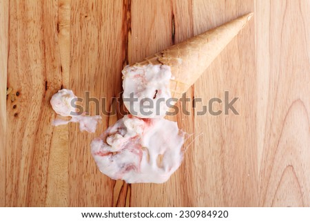 ice cream cones dropped on wooden background - stock photo