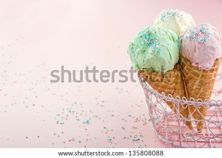 Ice cream cones in an metal basket in pink shabby chic vintage background - stock photo