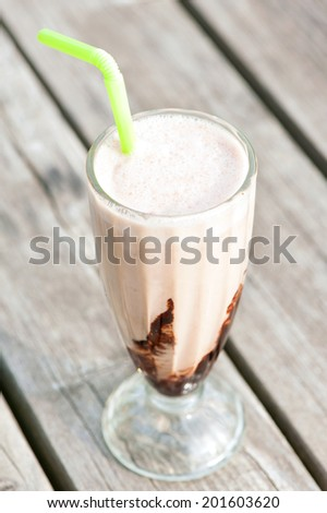 Ice-cream milkshake with chocolate on wooden background. Protein snack. Outdoors closeup. - stock photo