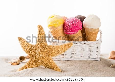 Ice cream scoops on sandy beach, close-up. - stock photo