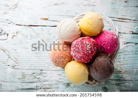 Ice cream scoops on wooden table, close-up. - stock photo