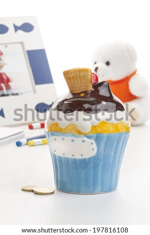 Ice cream shaped money box with toys on white wooden background. - stock photo