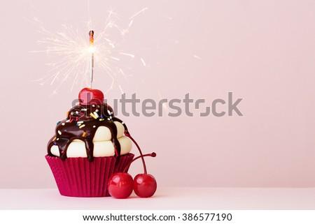 Ice cream sundae cupcake with sparkler - stock photo
