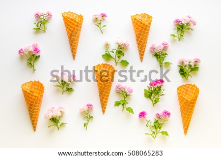 Ice cream waffle cones and chrysanthemum  flowers on the white wooden background. Top view.