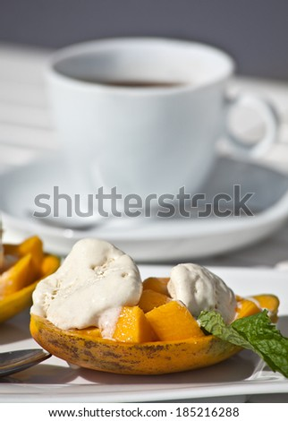 Ice-cream with mango and the white Cup on the table cafe - stock photo