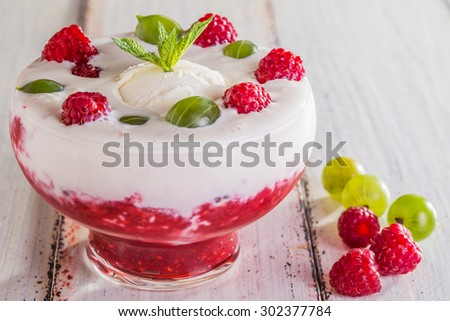 Ice cream with raspberry mousse and berries - gooseberries and raspberries on a white background.