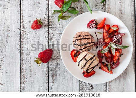 Ice cream with strawberries and chocolate on a white plate.Top view - stock photo