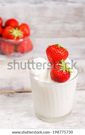 ice cream with strawberry on a white wood background. toning.selective focus on  strawberry on the ice cream
