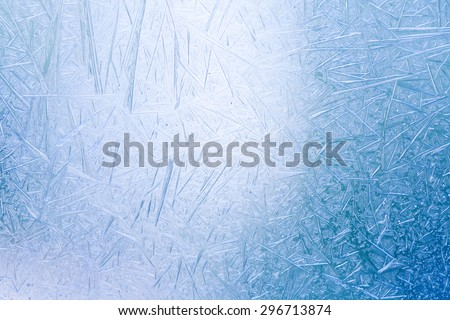 Ice crystals formed on the inside surface of windows. Blue and white color. frosting window closeup.