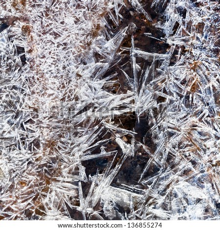 ice crystals under frozen stream in spring forest - stock photo