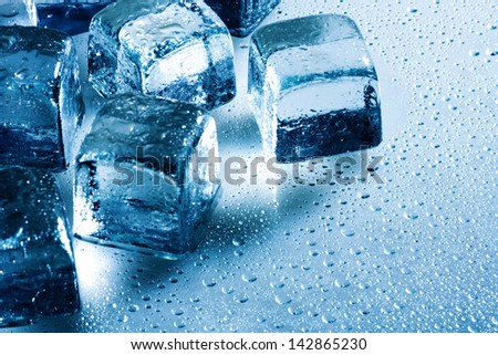 Ice cube and water drops on the wet background - stock photo
