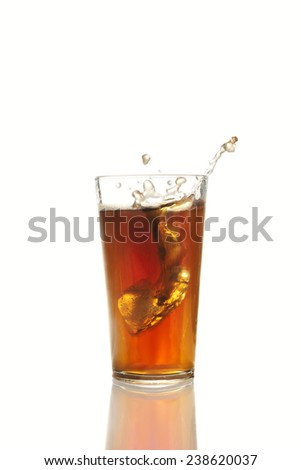 Ice cube falling into glass of cola