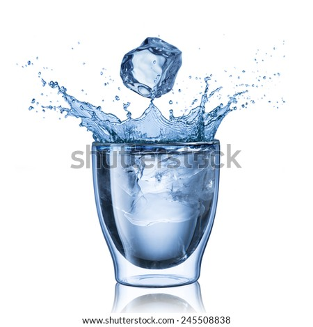 Ice Cube Falling Into Glass of Water Causing Splash - stock photo