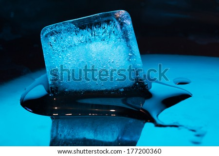 ice cube in blue on a black background - stock photo