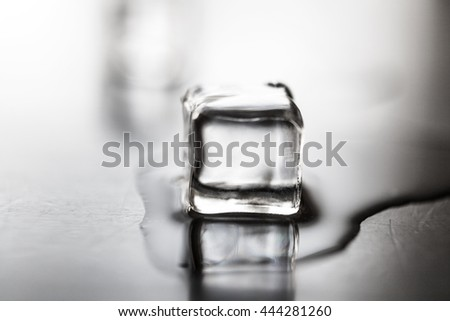 Ice cube melts on table with reflection - stock photo