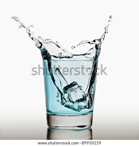 Ice cube splashing in a cool glass of water - stock photo