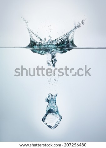 Ice cube splashing into clear water surface view - stock photo
