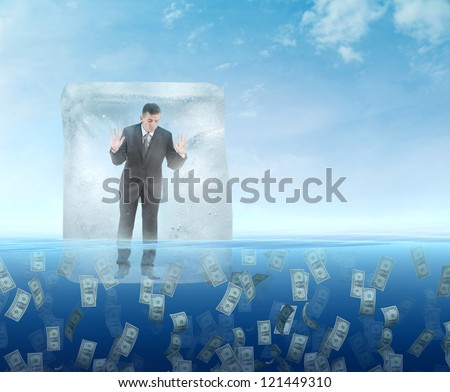 Ice cube with a businessman  floating in the sea of money - stock photo