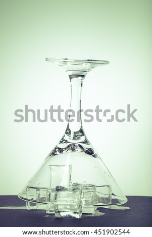 Ice cubes and martini glass on white background. Toned.
