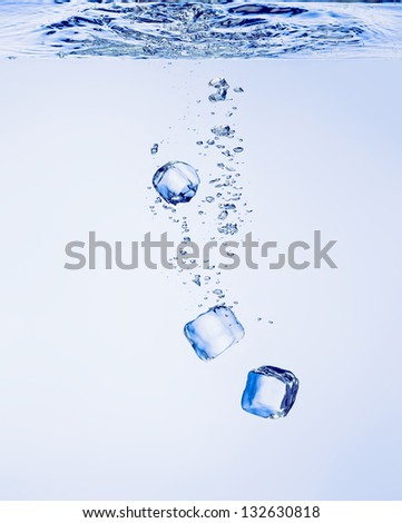 Ice cubes falling in clear water, with bubbles - stock photo
