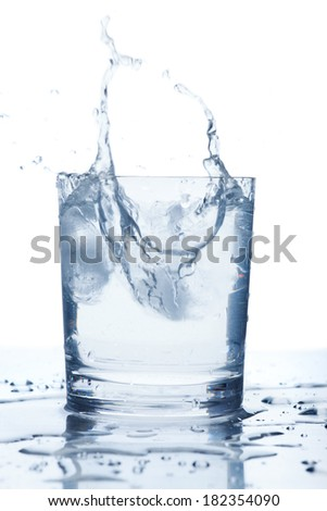 ice cubes falling into a glass of water  - stock photo