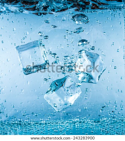 Ice cubes falling into the water sinking to the bottom. Abstract background. - stock photo