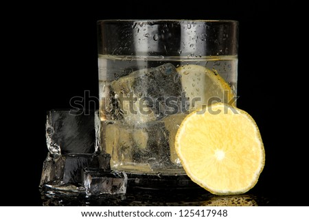 Ice cubes in glass with lemon isolated on black