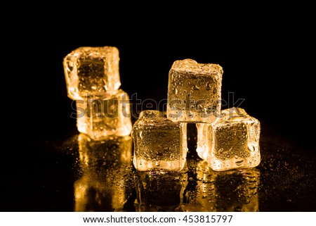 Ice cubes of gold color on a reflective surface.