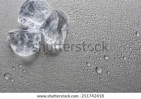 Ice cubes on a metallic surface with droplets