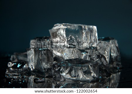 Ice cubes on dark blue background - stock photo