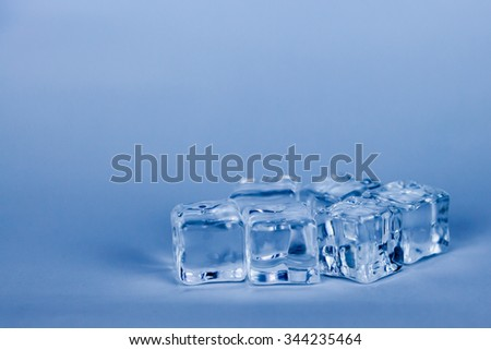 Ice cubes on grey background (blue cooling style) - stock photo
