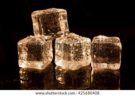 ice cubes on reflection black background. - stock photo