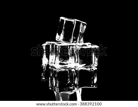 ice cubes on reflection table on black background - stock photo