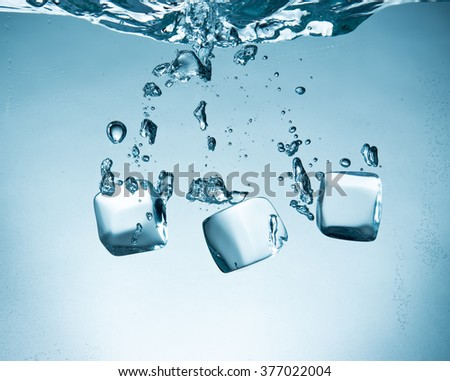 Ice cubes splashing into water, close-up - stock photo