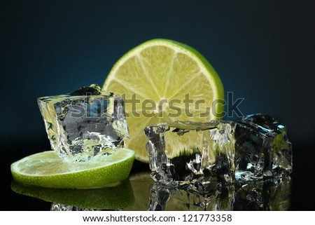Ice cubes with lime on darck blue background - stock photo