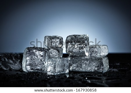Ice cubes with water splash on wet black surface - stock photo