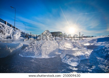 Ice figures on a frozen lake in a winter sunny day with blue sky - stock photo