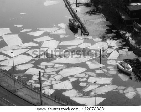 Ice floes in a small harbor with small boats
