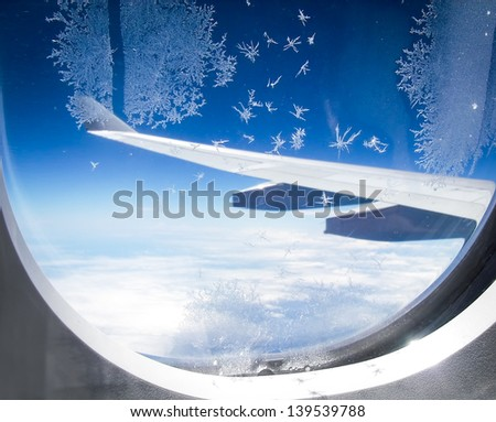 Ice flowers on airplane window, with wings in background - stock photo