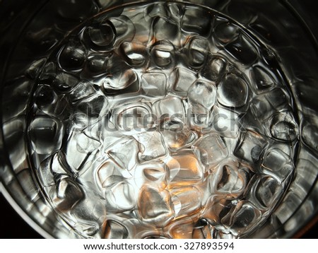 Ice for cooling drinks and cocktails in a large cup at the bar