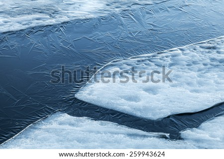 Ice fragments and thin layer of frozen river water. Dark blue natural background - stock photo