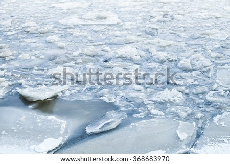 Ice fragments covered with show on cold river water. Dark blue natural winter background - stock photo