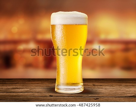 Ice Gold Beer glass on the background of the bar pub, on the wooden table and orange bokeh effect background,