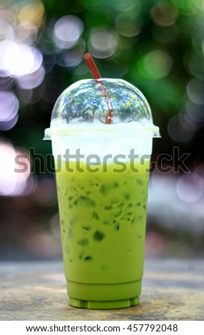 Ice green tea in plastic cup and background