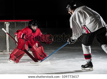 Ice hockey action shot with forward player and goalie.