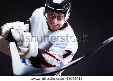 Ice-hockey player holds stick - stock photo
