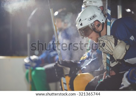ice hockey players,  group of team friends waiting on bench to start  game - stock photo