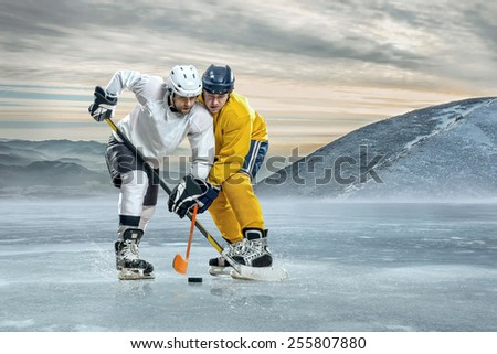 Ice hockey players on the ice in mountains - stock photo