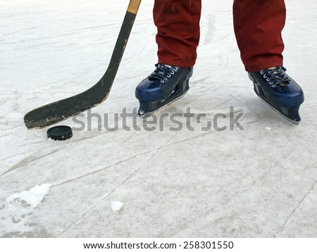 Ice hockey puck and kick and legs with skates        - stock photo